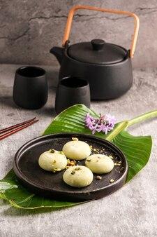 회색 배경에 일본 전통 달콤한 음식인 피스타치오 아이스크림을 넣은 떡