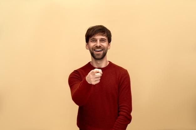 モック、面白いジョーク。セーターを着て、指と歯の生えたラフを指して、ベージュの壁に向かってポーズをとっているひげを持つ若い男の写真。
