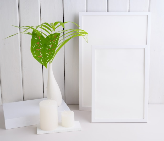 Mock uo poster frame and  palm leaves  botanical tropical house plant in beautiful white ceramic vase on white table  wall background