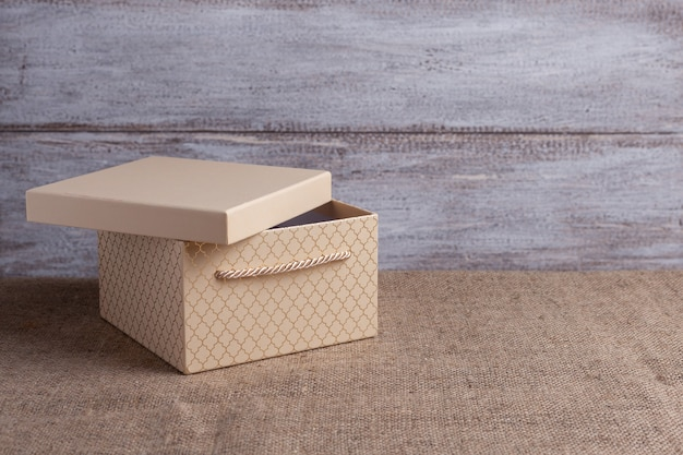 Mock up of a beige gift box with an open lid