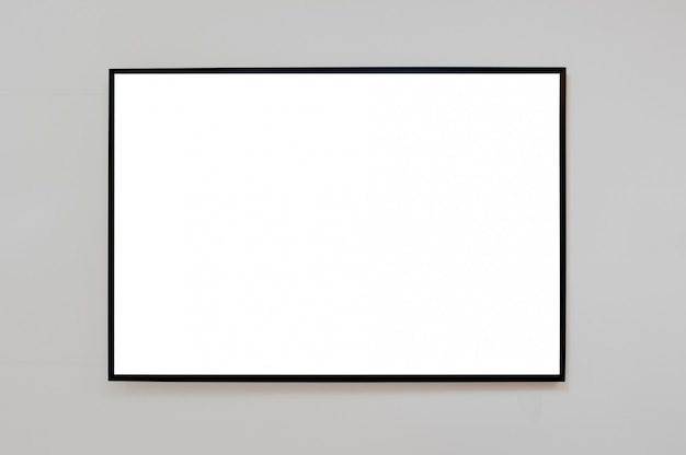 Mock up black frame for picture, advertisement or poster on a gray wall