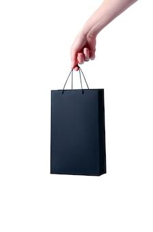 白い背景の上の女性の手でモックアップ黒のショッピング紙袋。