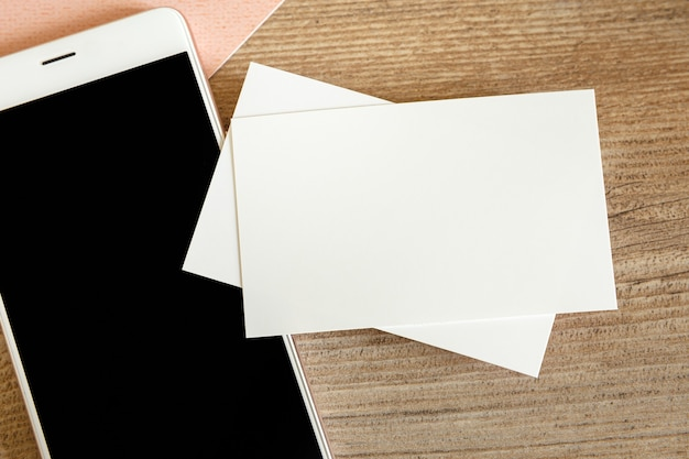 Mock up of blank business card and black smartphone screen on table