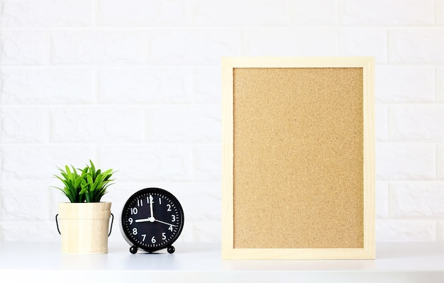 Mock up blank cork board with watch,green plants on white brick wall,minimal style