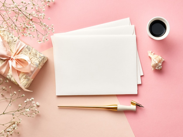 Mock up of blank envelopes on pink or beige background with calligraphy
