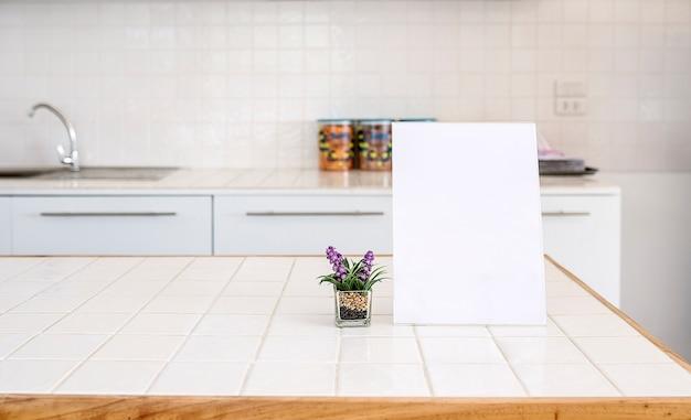 부엌 방에 테이블에 빈 메뉴 프레임과 관엽 식물 오순절 복사 공간을 조롱