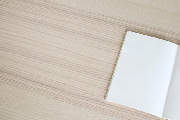 木製のテーブルの背景に空白の開いた紙の本をモックアップ