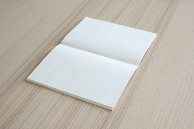 Mock up blank open paper book on wood table