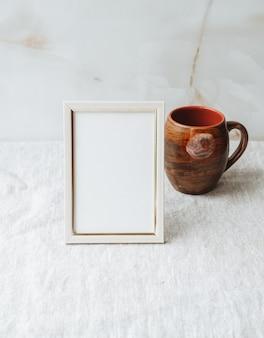 테이블에 빈 사진 프레임을 모의 회색 린넨 식탁보 패브릭 배경 홈 오피스 장식
