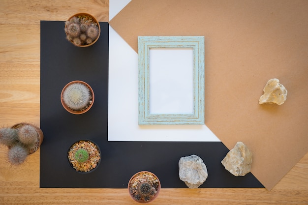 Mock up of blank photo frame with cactus on wood background, simple and minimal style