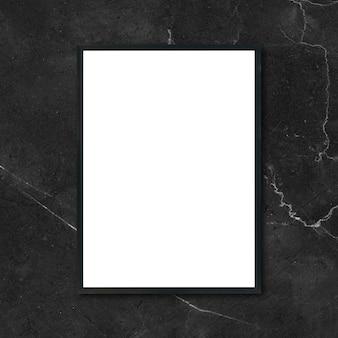 部屋の黒い大理石の壁にぶら下がっている空のポスターの額縁をモックアップする - モンタージュ製品の表示とデザインのキービジュアルレイアウトのモックアップに使用できます。