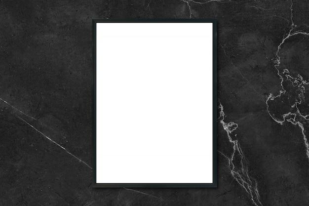 Макет пустой плакат фоторамки висит на черной мраморной стене в комнате