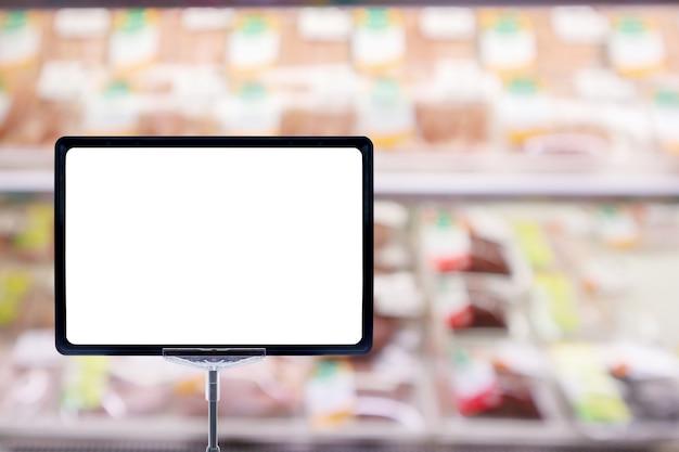 スーパーマーケットの食料品店の抽象的な新鮮な肉の棚で空白の価格ボードのポスターサインディスプレイをモックアップボケ光でぼやけた焦点ぼけの背景