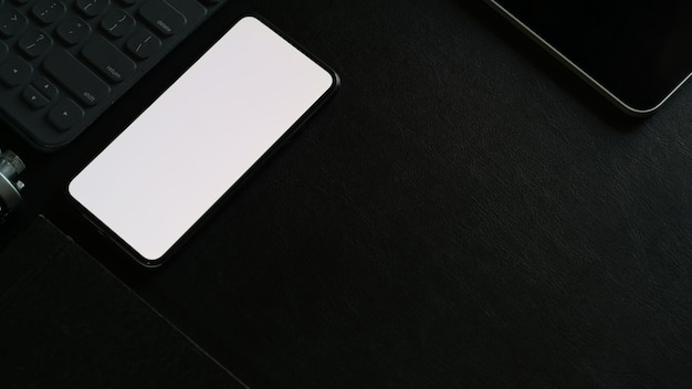 Mock up blank screen mobile phone and office accessory on dark office desk