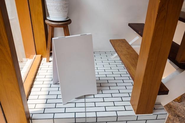 木造住宅の床に立っている空白の白い通知看板をモックアップ