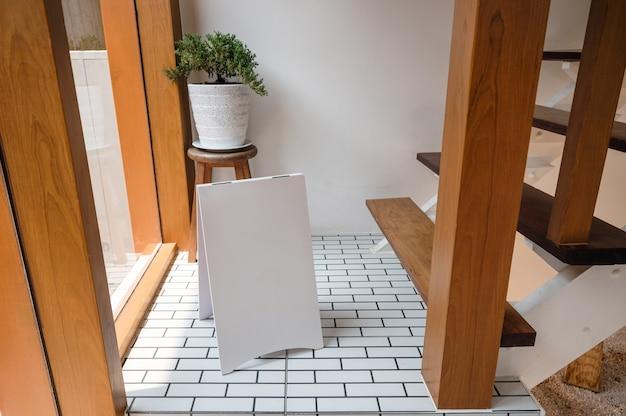 木造住宅の床に花瓶に植物と立っている空白の白い通知看板をモックアップ