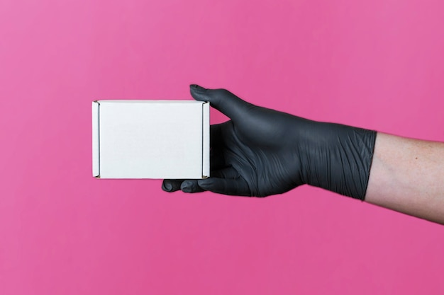 Mock-up of a box of white cortona in a female hand in black medical gloves on a colored background. space for text