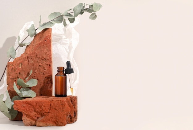 Mock up brown glass bottle with dropper serum on red stone and beige background with crumpled paper. brutal. copy space. acid peeling, face oil, collagen