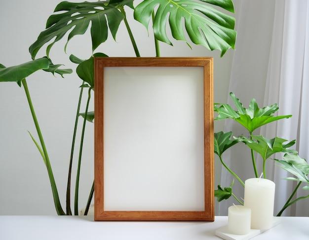 茶色のポスターフレーム、ベージュのテーブルと壁の背景、白い柔らかいトーンのインテリアにガチョウの植物フィロデンドロン緑の葉と香りの白いキャンドルをモックアップ