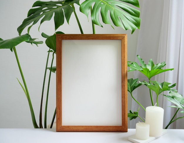 Mock up brown poster frame, gouse plant philodendron green leaf and aroma white candles on beige table and wall background,white soft tone interior