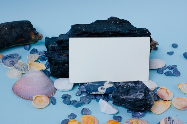 Mock up business card with wooden, sea shell and stone decor on blue