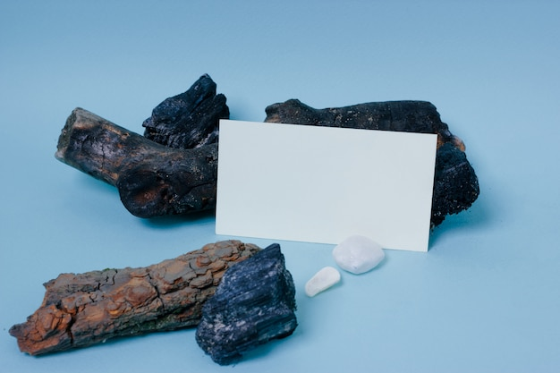 Mock up business card with wooden and stone decor on blue