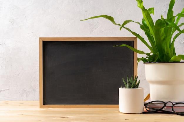 デザインコンクリートの美しいサボテンと植物で木製のテーブルにチョーク黒板フレームをモックアップ