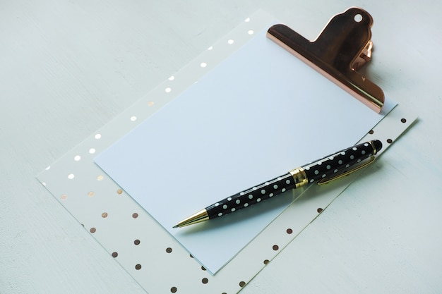 Mock up clipboard and black white polka dot pen on white table.
