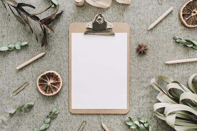 Mock up clipboard in frame of dry leaves and oranges, eucalyptus branches on beige rustic blanket background. flat lay, top view