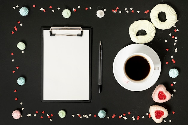 Mock-up clipboard with cup of coffee surrounded by meringue cookies