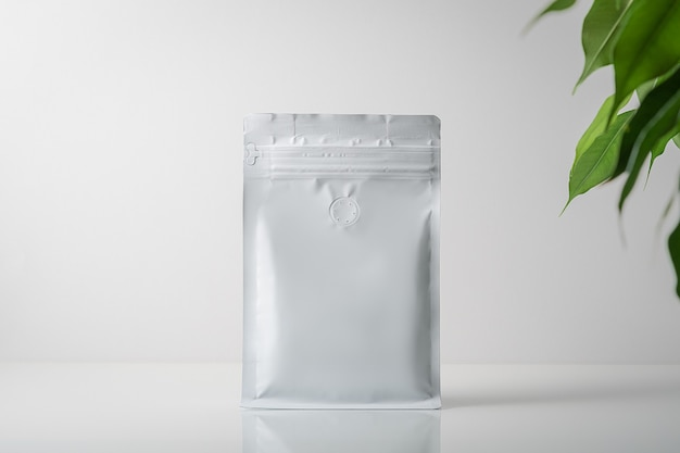 Mock-up of a coffee bag on a gray background with green leaves. coffee gray bag with zipper.
