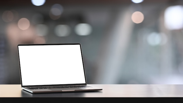 Mock up computer laptop with blank screen on wooden table and blurred office interior background.