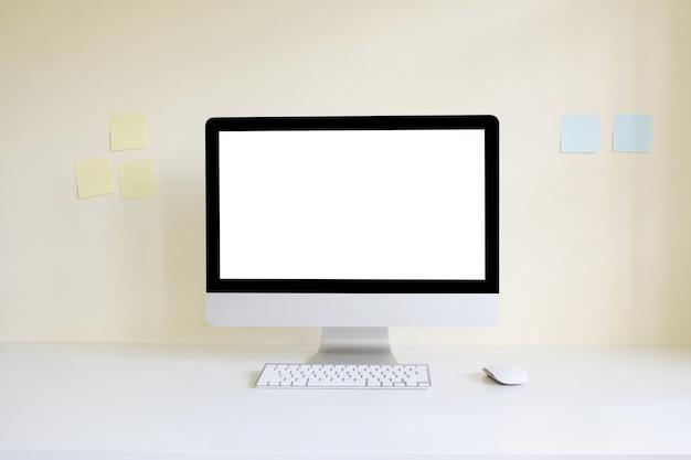 Макет компьютера на рабочем пространстве с пустой экран и заметки на стене.