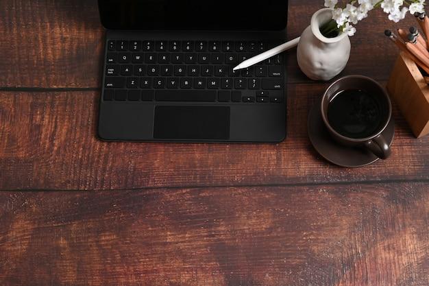 Копируйте компьютерный планшет, стилус и чашку кофе на деревянном столе.