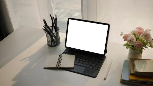 Копируйте компьютерный планшет с пустым зеленым, блокнотом, держателем для карандашей и цветами в удобном рабочем месте.