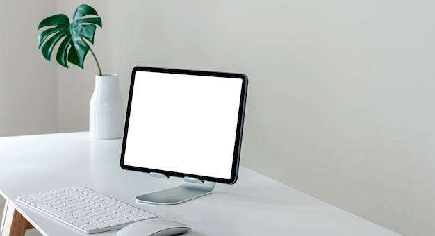 흰색 테이블에 빈 화면이 컴퓨터 태블릿을 모의