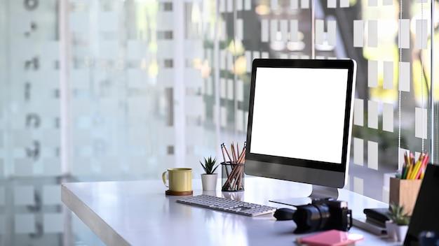 写真家のワークステーションに白い画面、カメラ、事務用品を備えたコンピューターをモックアップします。