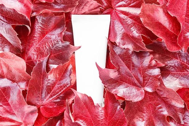Макет косметической трубки на фоне красных диких виноградных листьев. увлажняющий крем, шампунь, крем для рук