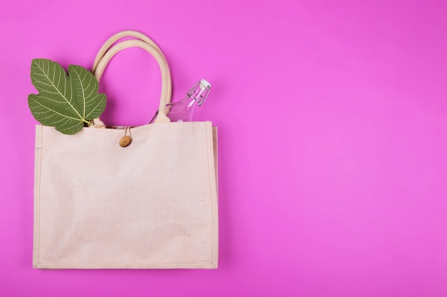 Mock up cotton bag with glass bottle and bamboo napkin on pink . eco minimalistic style. zero waste