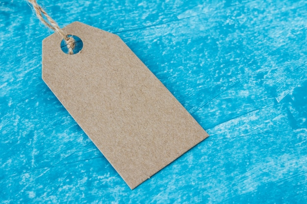 Mock up of craft paper tag label on blue