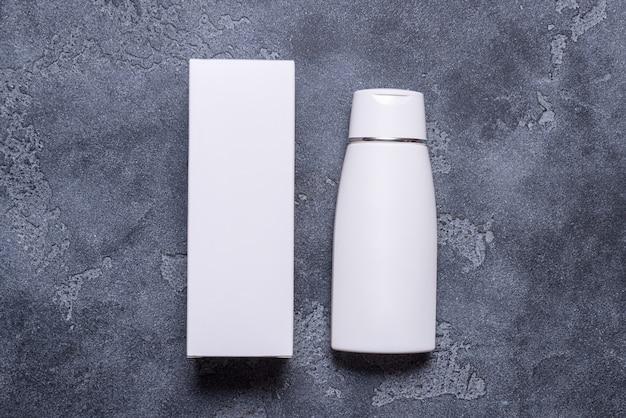 灰色の背景にモックアップ、クリーム色のボトルとカートンボックス
