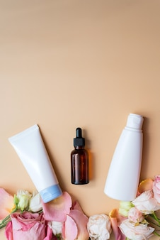 Mock-up cream and lotion in white packages and moisturizing serum in a brown glass bottle on a blue background next to rose petals. the concept of creating natural cosmetics.