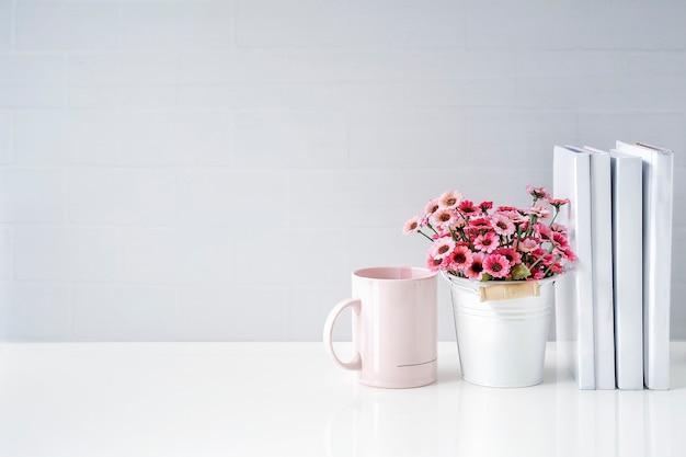 白い煉瓦の壁がある白いテーブルにカップ、本、観葉植物をモックアップする