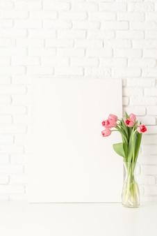 デザインをモックアップします。白いレンガの壁の背景にフレームとピンクのチューリップでモックアップ