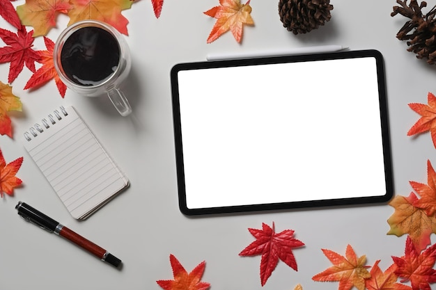 Mock up digital tablet, coffee cup, pine cone and maple leaves on white table.
