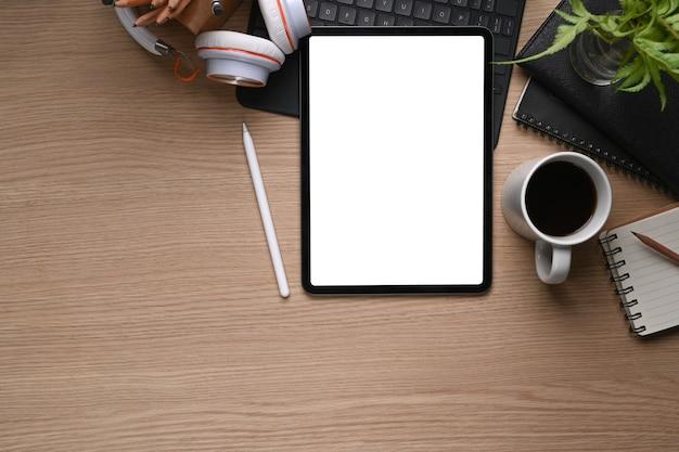 나무 테이블에 디지털 태블릿, 스타일러스 펜, 커피 컵, 헤드 폰을 비웃습니다.