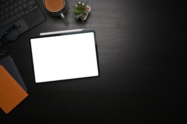 블랙 테이블에 디지털 태블릿, 스타일러스 펜, 노트북 및 커피 컵을 비웃습니다.