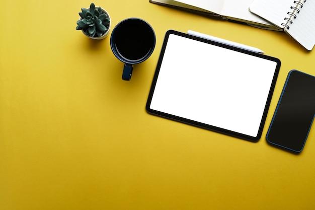 黄色の背景にデジタルタブレット、ジューシーな植物、ノートブック、スマートフォン、コーヒーカップをモックアップします。