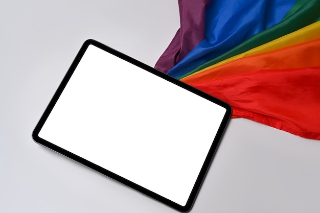 Mock up digital tablet with blank screen near rainbow flag on white background.