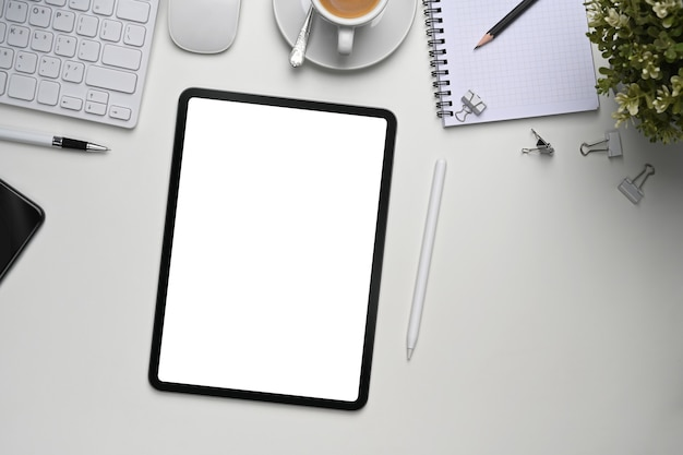 Mock up digital tablet with blank screen, plant and office supplies on white office desk.